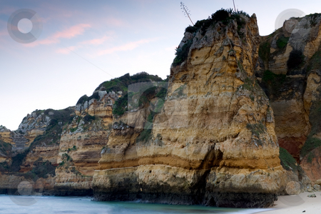 Sheer rocky cliffs stock photo, The sheer rocky cliffs at the beaches of 'Praia Dona Ana' in Lagos, Portugal, with a setting sunlit sky. by Kevin Woodrow