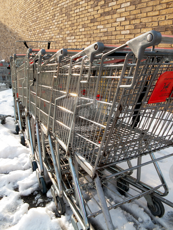 Where carts go to die stock photo, A bunch of old shopping carts, with a brick wall in the background, surrounded by snow. by Kevin Woodrow
