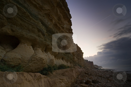 Early morning cliff walls stock photo, Cliff detail fading into an early morning sky, along the beaches in Lagos, Portugal. by Kevin Woodrow
