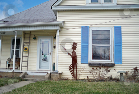 Say Uncle stock photo, Metal Uncle Sam yard decor against a country style house with front porch and blue shutters by Sandra Fann