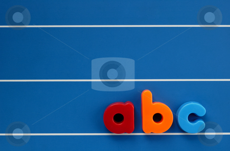 Child's letters stock photo, The letters a, b and c from a child's toy alphabet set, placed on a blue, lined background. Space for text elsewhere in the image. by Alistair Scott