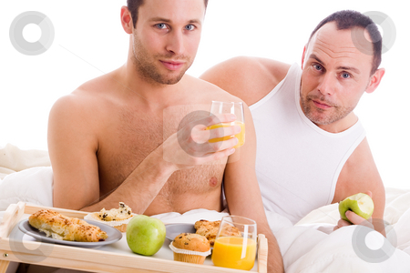 Homo couple enjoy their breakfast stock photo, A Happy homo couple and their breakfast on a tray in bed by Frenk and Danielle Kaufmann