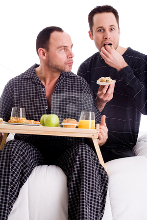 Home couple in pyama stock photo, A Happy homo couple and their breakfast on a tray in bed by Frenk and Danielle Kaufmann