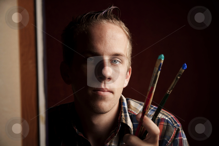 Handsome young artist stock photo, Handsome young artist holding brushes by Scott Griessel
