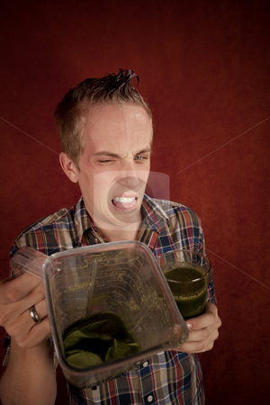 Young man with unappetizing health shake stock photo, Young man grimacing and holding unappetizing blended health shake by Scott Griessel