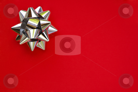 Star on red stock photo, A decorative star, made from silver ribbon, on a plain red background with space for text (copy). by Alistair Scott