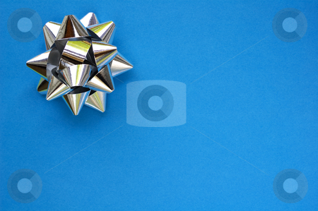 Star on blue stock photo, A decorative star, made from silver ribbon, on a plain blue background with space for text (copy). by Alistair Scott