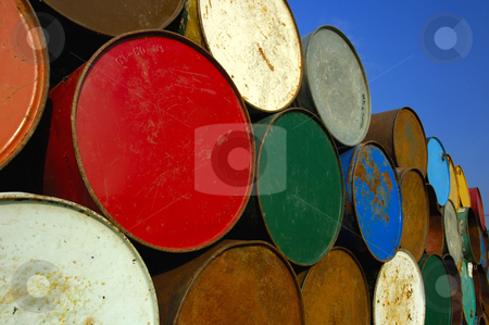 Oil barrels stock photo, A stack of multi-coloured oil barrels, towering in to the clear blue sky. Space for text in the sky. by Alistair Scott
