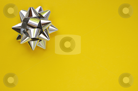 Star on yellow stock photo, A decorative star, made from silver ribbon, on a plain yellow background with space for text (copy). by Alistair Scott