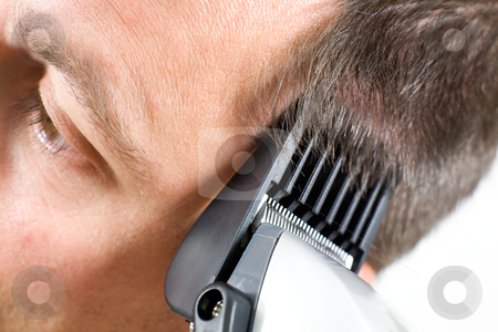 Head shaving stock photo, A man getting a haircut with clippers by Laurent Renault