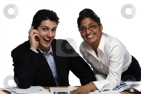 Teamwork - Smiling stock photo, Businesswoman standing helping her male colleague who's seated.  Both are looking at the camera.  Shot horizontal isolated on white. by Orange Line Media
