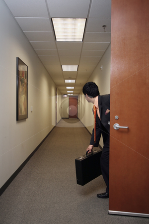 Businessman and his briefcase stock photo, Businessman looking around suspiciously with his briefcase in hand in an empty hallway by Orange Line Media