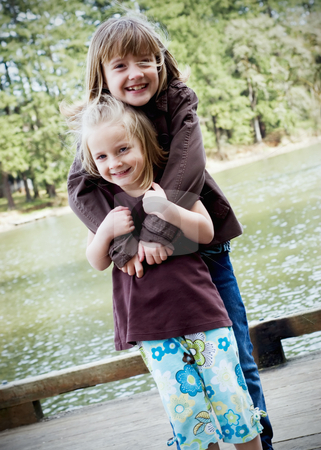Sisters Hugging stock photo, Vertically framed shot of two cute sisters hugging in a park by Orange Line Media