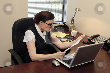 Woman Reading a Letter - Horizontal stock photo, Horizontally framed shot of a businesswoman at her desk reading a letter containing bad news by Orange Line Media