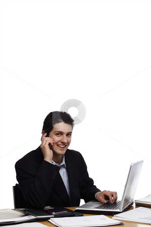 Businessman Looking at You, Calling Smiling stock photo, Businessman, sitting at a desk, calling and smiling at the camera.  Vertical isolated on white. by Orange Line Media