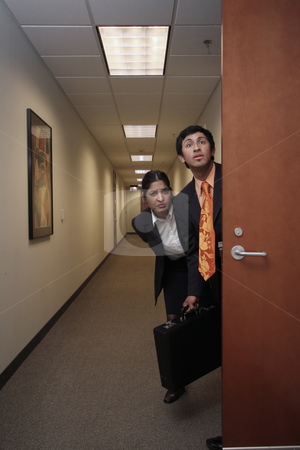 Man and Woman in Hallway stock photo, A shot of a businessman and businesswoman sneaking out of an office. Both looking in the same direction. by Orange Line Media