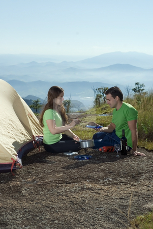 Couple Camping, Cooking with View - Vertical stock photo, Young smiling couple, sitting next to a tent, cooking on cookstove.  In the background are beatiful clouds and mountains. by Orange Line Media