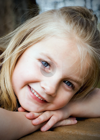 Young Blonde Girl - Vertical stock photo, Cute blond girl resting her head on her arms smiling at the camera. Vertically framed shot. by Orange Line Media