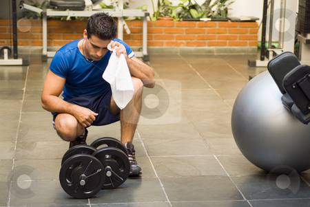 Athlete Toweling Brow stock photo, Male athlete kneeling down by dumbbells toweling sweat of his brow. by Orange Line Media