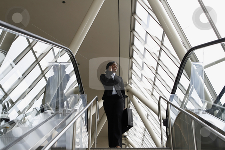 Businesswoman on Stairs - Horizontal stock photo, Attractive businesswoman smiling and talking on her phone as she stands at the top of the stairs by Orange Line Media