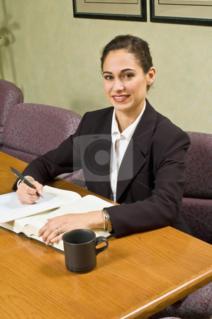 Businesswoman Looking into Camera stock photo, Young, seated businesswoman looking into camera. by Orange Line Media