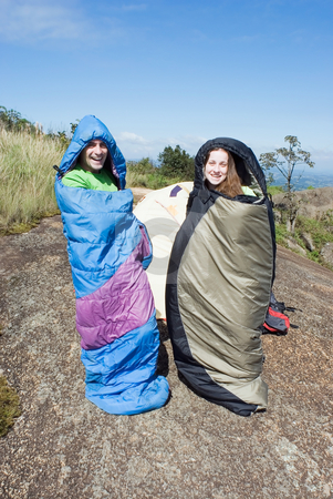 Rise and Shine stock photo, Attractive couple standing and smiling in their sleeping bags. Humorous by Orange Line Media