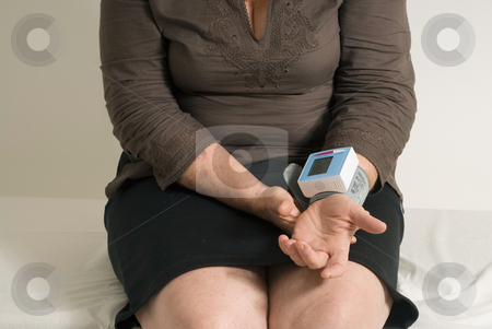 Self Checking Blood Pressure - Horizontal, Isolated stock photo, Mid-body shot of a middle-aged woman checking her blood pressure with a machine. by Orange Line Media