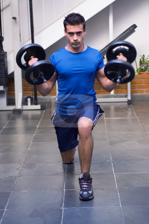 Lunges with Dumbbell Weights stock photo, Male athelete / weightlifter, looking straight into camera, doing lunges with dumbbell weights in his hands. by Orange Line Media