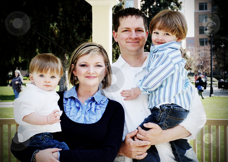 Family Portrait stock photo, Cute family of four standing in the sun as they get their picture taken by Orange Line Media