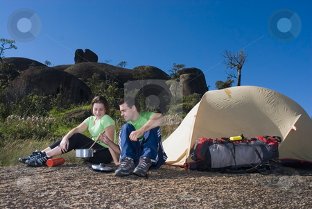 Couple Cooking Out stock photo, Young attractive couple on a camping trip cooking a meal in front of their tent by Orange Line Media