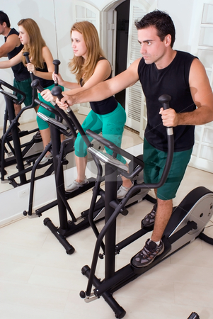 Couple at the Gym stock photo, Attractive couple on elliptical trainers at the gym. Vertically framed shot. by Orange Line Media