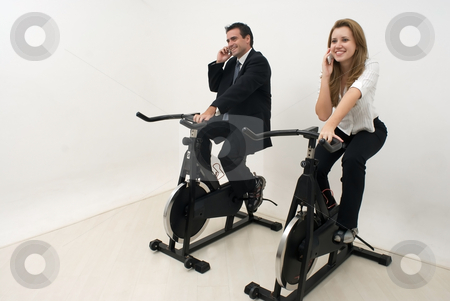 Businesspeople at the Gym - Horizontal stock photo, Businessman and businesswoman dressed in suits riding on exercise bikes and chatting on their cellphones by Orange Line Media