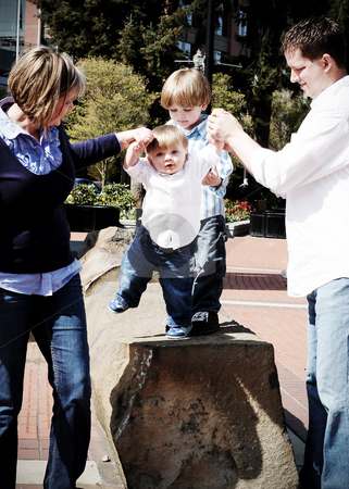 Family Fun stock photo, Attractive young family of four playing together in the park. Vertically framed, high-contrast shot. by Orange Line Media