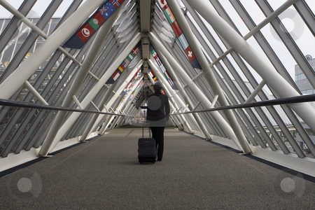 Businesswoman in Walkway stock photo, Businesswoman walking through a walkway / skybridge pulling her luggage behind her. The walkway is lined with flags. Horizontally framed shot with the woman walking away from the camera. by Orange Line Media