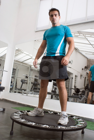 Athlete Standing on Trampoline stock photo, Muscular athlete, looking into the camera, standing on trampoline in a gym. by Orange Line Media