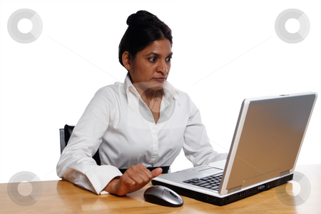 Businesswoman at Desk Surprised by Laptop stock photo, Isolated businesswoman sitting at a desk looking very surprised and concerend at her laptop. by Orange Line Media