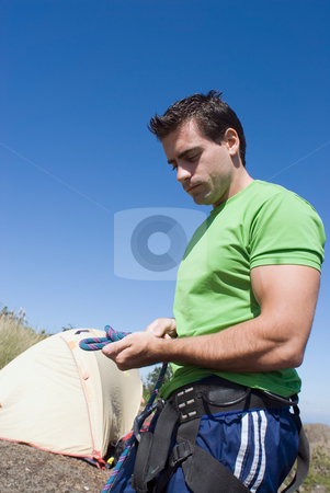 Male Rock Climber - Vertical stock photo, Side profile of an athletic, handsome male rock-climber checking his rigging and ropes. Set against a blue sky. by Orange Line Media
