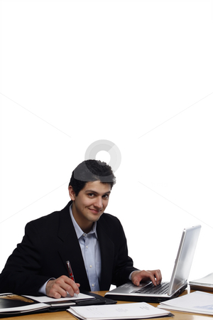 Businessman Looking at You stock photo, Businessman, sitting at a desk, writing and smiling at the camera.  Vertical isolated on white. by Orange Line Media