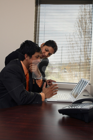 Business Team Looking Stumped - Vertical stock photo, Male and female business colleagues working together on a hard problem. They have a strained expression on their faces by Orange Line Media