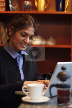 Woman working in a Cafe stock photo, Businesswoman working on a laptop in a cafe. Vertically framed shot. by Orange Line Media