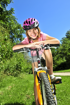 Teenage girl on a bicycle stock photo, Portrait of a teenage girl on a bicycle in summer park outdoors by Elena Elisseeva