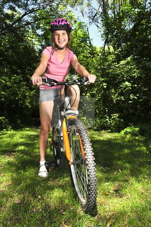Teenage girl on a bicycle stock photo, Portrait of a teenage girl on a bicycle in summer park outdoors by Elena Elisseeva