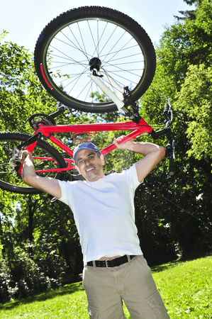 Man carrying a bicycle stock photo, Happy middle aged man with his bicycle in summer part by Elena Elisseeva