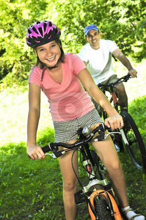 Family on bicycles stock photo, Teenage girl and her father riding bicycles in summer park by Elena Elisseeva