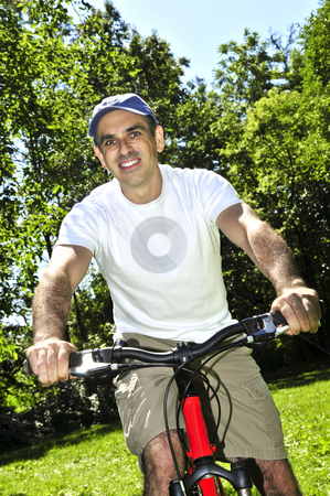 Man riding a bicycle stock photo, Happy middle aged man riding a bicycle in summer part by Elena Elisseeva