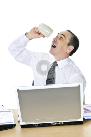 Overworked businessman at his desk on white background stock photo, Overworked businessman with coffee mug at his desk isolated on white background by Elena Elisseeva