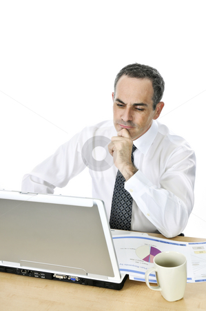 Businessman at his desk on white background stock photo, Thoughtful businessman sitting at his desk isolated on white background by Elena Elisseeva