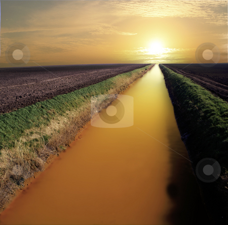 River of gold stock photo, Straight and narrow river flowing towards infinity and the sunset. Looking like liquid gold by Paul Phillips