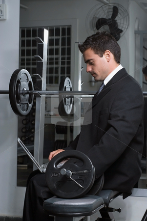 Businessman at the Gym with Laptop - Vertical stock photo, Side-shot of a handsome businessman, wearing a suit, sitting on bench using a laptop. by Orange Line Media