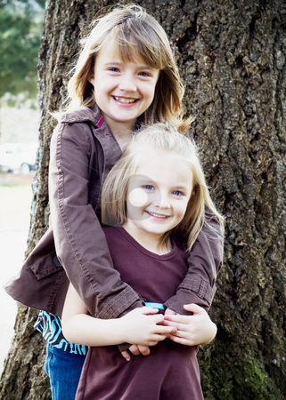 Smiling Sisters stock photo, Two young caucasian sisters holding each other and smiling in front of a tree by Orange Line Media
